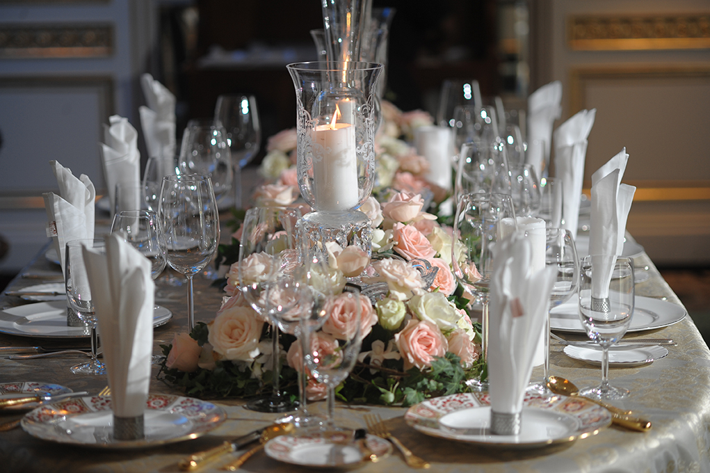 View of an elaborate table decoration with candles, flowers and glasses